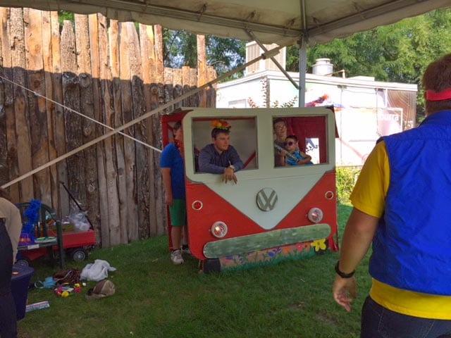 kids posing behind a cardboard Volkswagon bus.