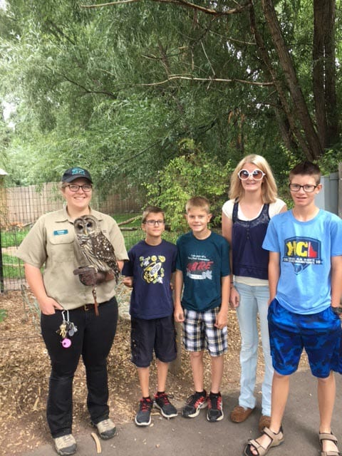 Group of kids next to a zoo employee holding an owl.