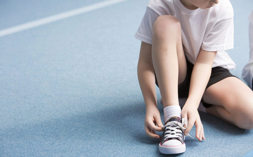 Child with type 1 diabetes tying shoe.