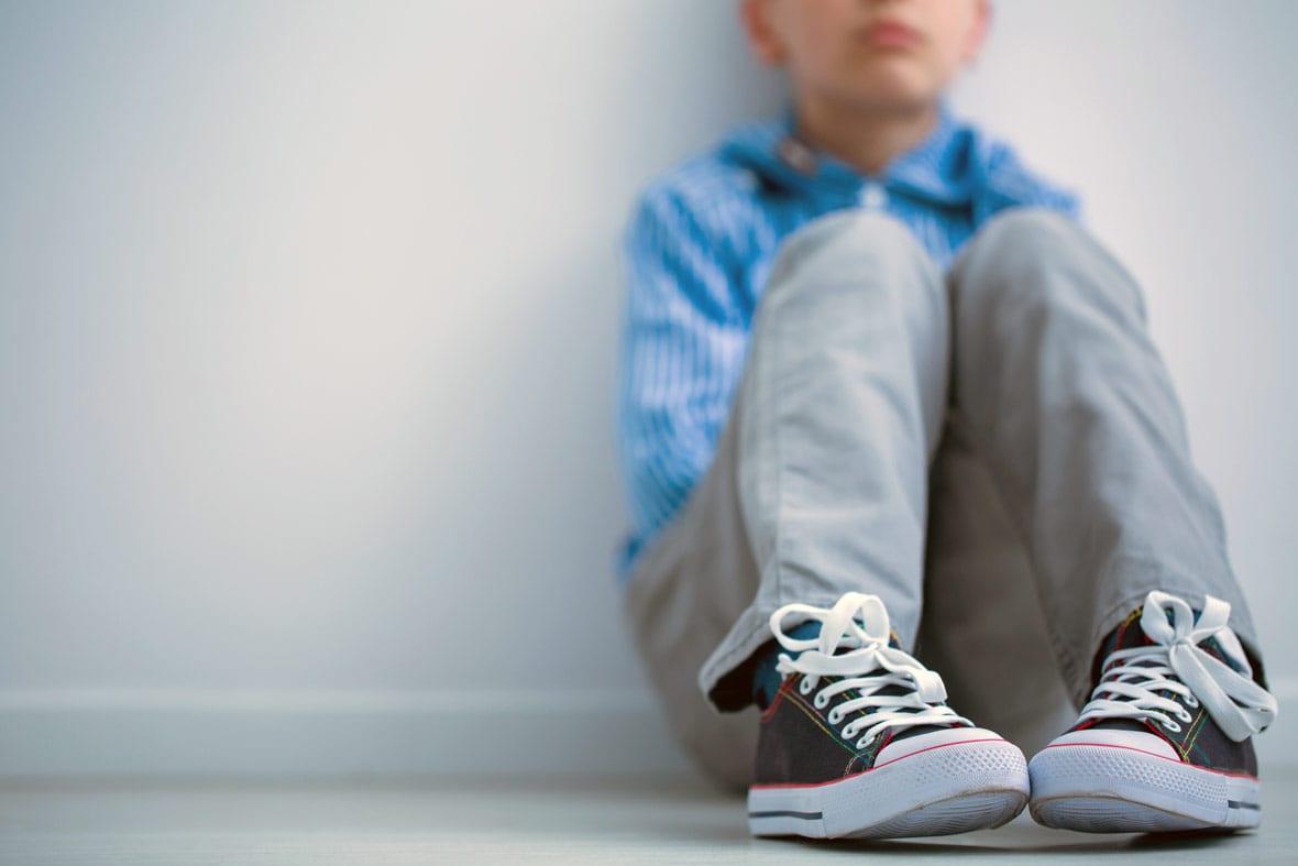 Tired boy sitting on floor.